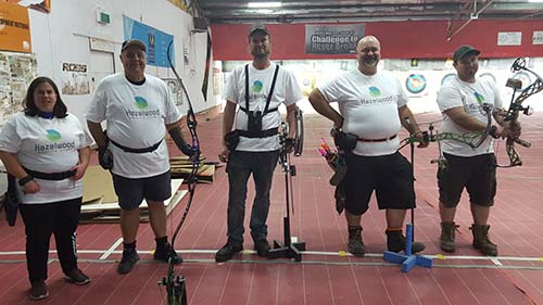 One woman and four men standing in a line with their bows at an indoor archery range.
